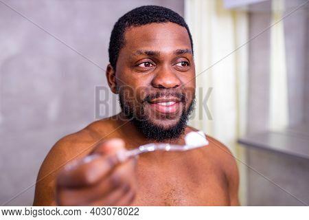 Africa Man Toothbrush In Bathroom Looking At Mirror
