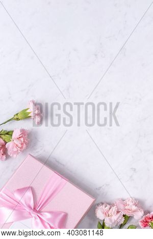 Top View Of Beautiful Carnation And Gift On Marble White Table Background.