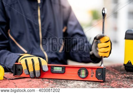 Male Mechanic Hand Or Maintenance Worker Man Wearing Protective Suit Holding Wrench And Aluminium Sp