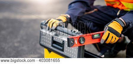 Male Mechanic Or Maintenance Worker Man Holding Red Aluminium Spirit Level Tool Or Bubble Levels And
