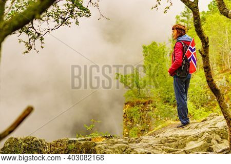 Tourist Woman With Norwegian Flag In Hazy Foggy Mountains Nature