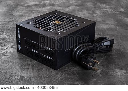 Varna, Bulgaria, January 11, 2021. Cougar Gex 80 Plus Gold Certified Psu And Power Cord On A Dark Ba