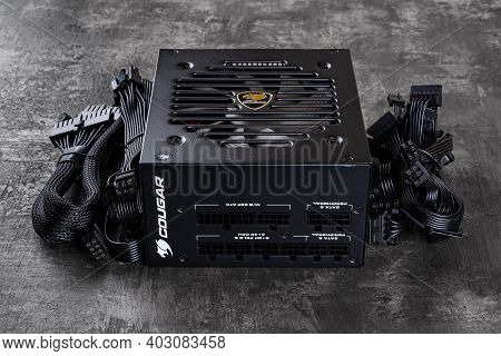 Varna, Bulgaria, January 11, 2021. Cougar Gex 80 Plus Gold Certified Psu And Set Of Power Cords On A
