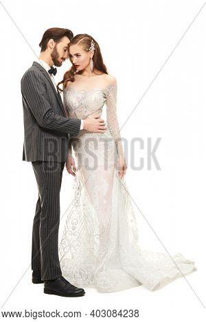 Full length portrait of a gorgeous woman and handsome man in luxury evening dresses on a white background. Fashion and holidays. Wedding fashion.