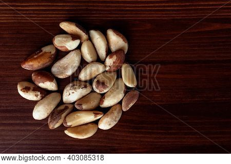 Pile Of Brazilian Nuts On Wooden Table. Brazil Nut Or Bertholletia. Top View