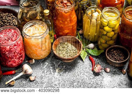 Marinated Vegetables With In Glass Jars. On A Rustic Background.