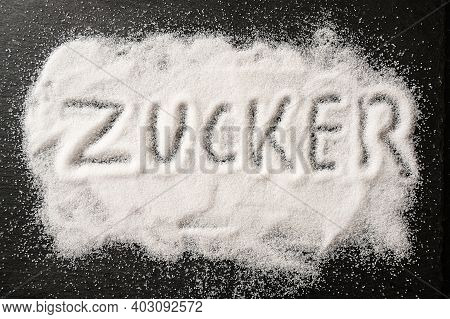 German Word Zucker, Meaning Sugar, Written In Spilled Out Sugar Crystals On A Dark Slate, High Angle