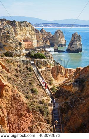 Lagos, Portugal - June 8, 2017 - Elevated View Of The Rugged Coastline With Steps In The Foreground,