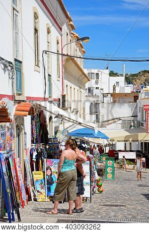 Albufeira, Portugal - June 10, 2017 - Tourists Looking At A Gift Shop Along An Old Town Shopping Str
