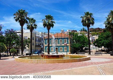Silves, Portugal - June 10, 2017 - Fountain In The Praca Al Mutamid With The Cathedral And Castle To