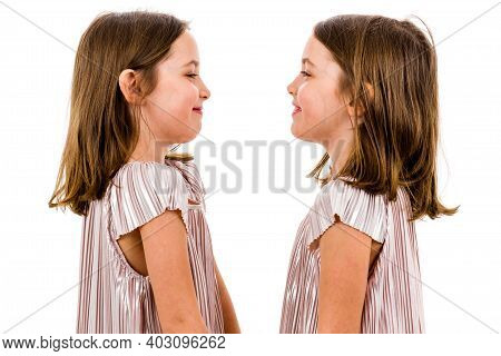 Identical Twin Girls Are Looking At Each Other And Smiling.
