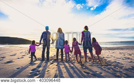 Family And Friends Group Standing On The Beach Holding Hands.