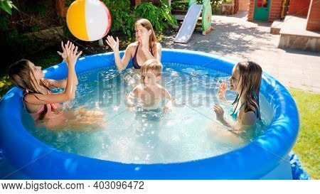 Happy Laughing And Cheerful Family With Children Having Fun And Playing In Swimming Pool At House Ba