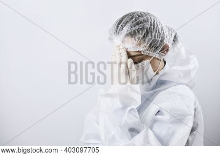 A Doctor In Protective Wear Looking Tired And Frustrated. Covid Combat Fatigue. Health Care Workers