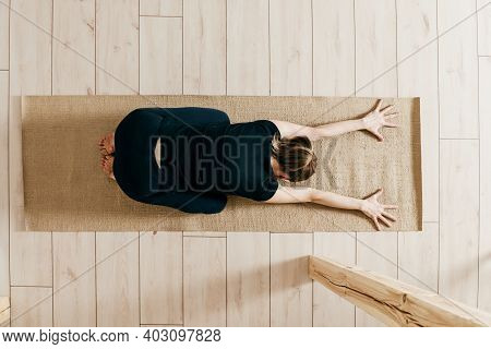 Top View Of Woman Woman Practicing Yoga Indoor. Woman Curls Up And Stretches Forward. Fitness Female