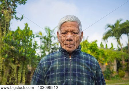 Portrait Of An Elderly Asian Man Smiling And Looking At The Camera While Standing In A Garden. Space