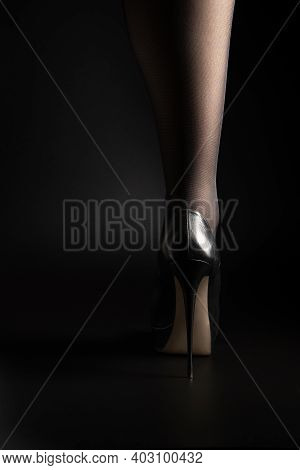 One Leg Of A Woman In Black Tights And High Heels On A Black Background.