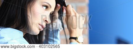 Portrait Of Woman Using Straightener On Brunette Long Hair. Cares About Hair. Hairdo. Female Person