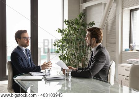 Serious Businessmen Talk Discuss Company Paperwork At Briefing