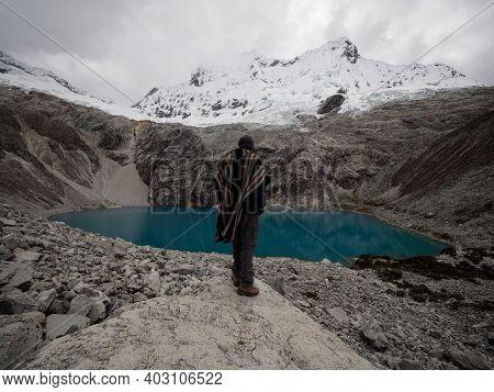 Hiker In Traditional Indigenous Poncho Cape At Andean Mountain Lake Laguna 69 Cordillera Blanca Huar