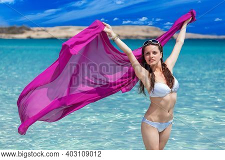 A Beautiful Woman In A White Swimsuit Posing With A Pink Silk Blanket On The Beach