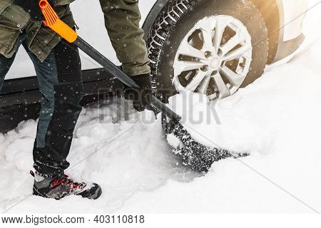 Man Is Shovelling Snow Near The Car In Winter Time. Winter Shoveling. Removing Snow After Blizzard
