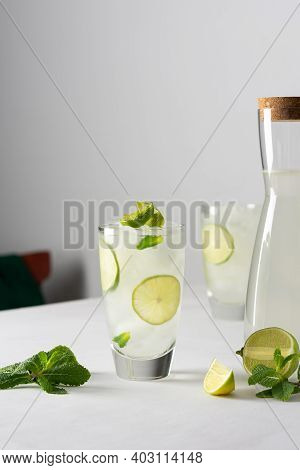 Refreshing Cold Drinks With Lime And Mint, Glasses With Lemonade And Ice, Jug With Drink On White Ba