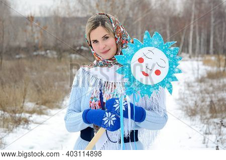 Young Russian Woman In A Shawl And Blue Mittens In A Winter Park. Portrait, Close-up