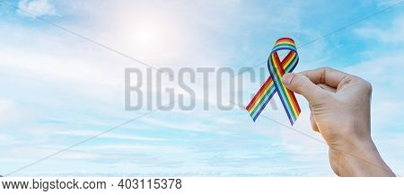 Hand Showing Lgbtq Rainbow Ribbon Against Sky Background In The Morning. Support Lesbian, Gay, Bisex