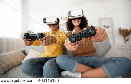 Females Roommates Have Fun On Couch In Cozy Interior With Video Games. Enthusiastic Smiling Teen Afr