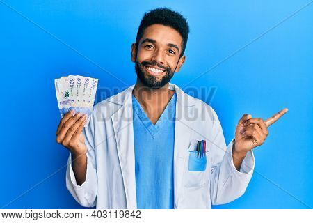 Handsome hispanic man with beard wearing doctor uniform holding 50 colombian pesos smiling happy pointing with hand and finger to the side