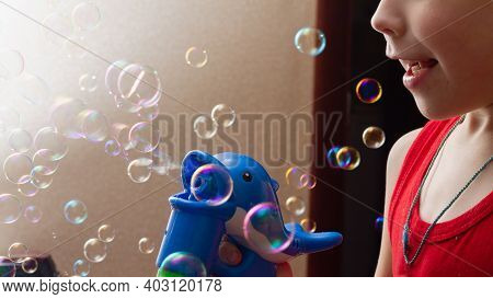 A Child Blows Soap Bubbles From A Gun At Home. A Lot Of Soap Bubbles Are Flying In The Air.