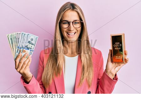 Young blonde woman wearing business style holding gold ingot and dollars smiling and laughing hard out loud because funny crazy joke.