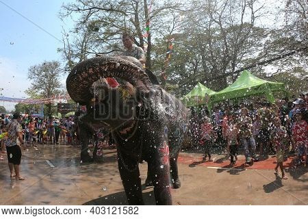 Ayutthaya , Thailand - April14 , 2019 : Mahout And His Elephant Playfully Splashing Water. Young Ele