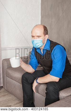 Sad Man Wearing Medical Mask With Headache Holding Cup With Hot Drink At Home
