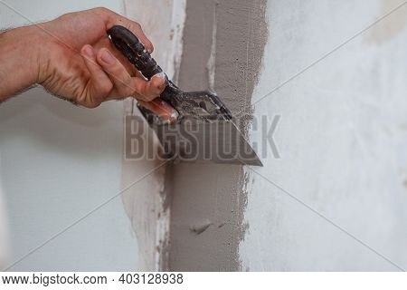 Man Hand With Trowel Plastering A Wall, Skim Coating Plaster Walls.