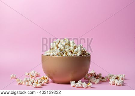 Popcorn On A Pink Background. A Full Plate Of Popcorn. Popcorn Is Scattered Around. Movie Snack