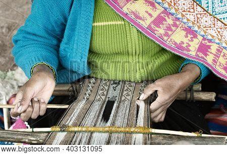 Native Peruvian Woman Weaving Intricate Llama Wool Garments Using A Traditional Hand Loom