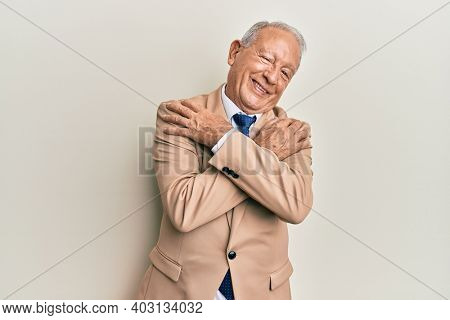 Senior caucasian man wearing business suit hugging oneself happy and positive, smiling confident. self love and self care