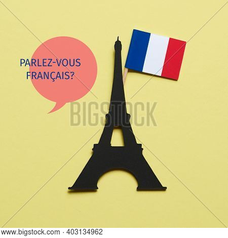 the eiffel tower, cutout on a black paperboard, the french flag and the question do you speak french written in french, on a yellow background