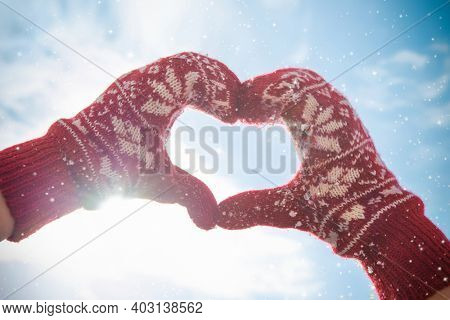 Woman hands in winter gloves make the shape of heart sign. Love and romance concept with sunset light on background