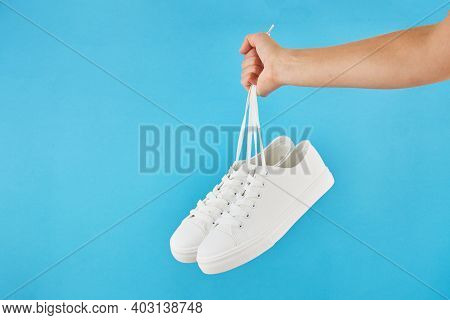 The Hand Holds By Shoelaces Pair Of Fashion Stylish White Sneakers On Pastel Blue Background.