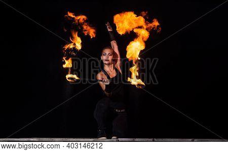 High Energy Firedancer. Sensual Firedancer Twirl Flaming Baton In Darkness. Fire Performance. Art Sh