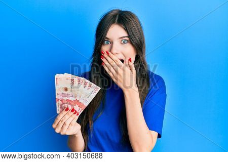 Young beautiful caucasian girl holding 10 colombian pesos banknotes covering mouth with hand, shocked and afraid for mistake. surprised expression