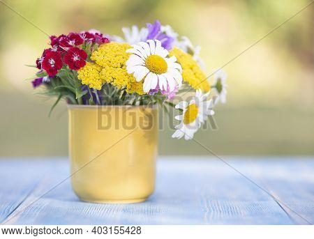 A Beautiful Bouquet Of Different Flowers Camomiles And Phloxes In A Yellow Glass On A Blue Table In