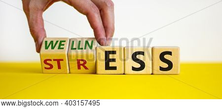 Wellness Instead Of Stress Symbol. Hand Turns Cubes And Changes The Word 'stress' To 'wellness'. Bea
