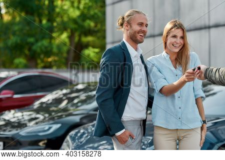 Cheerful Young Caucasian Couple Receiving Car Key From Dealer Hand While Standing Together In Luxury
