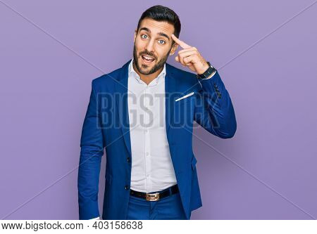 Young hispanic man wearing business jacket smiling pointing to head with one finger, great idea or thought, good memory