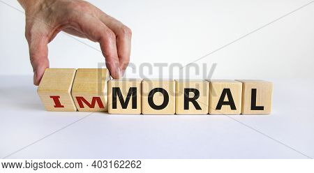 Moral Or Immoral Symbol. Hand Turns Cubes And Changes The Word 'immoral' To 'moral'. Beautiful White