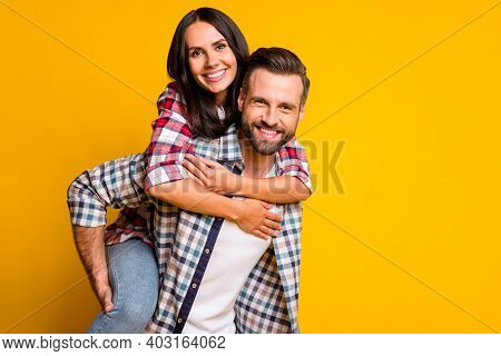 Photo Portrait Of Girl Piggyback Riding Guy Isolated On Vivid Yellow Colored Background